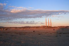 At a beach during sunset. Beach and 3 chimneys of a power plant in a back. Morro Bay, California Stock Photography
