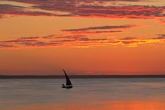 Beach sunset. Scene in Mozambique with small sailboat (called a dhow Stock Images