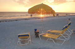 Beach sunset. Beach chairs and umbrellas at sunset, Clearwater, Florida Stock Photos