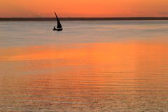 Beach sunset. Scene in Mozambique with small sailboat (called a dhow Stock Photography