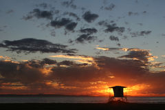 Beach sunset. Lifeguard tower with setting sun behind Royalty Free Stock Photo