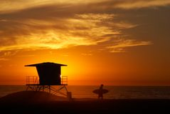 Beach sunset. Lifeguard tower with setting sun on the horizon and the silhouette of the surfer Stock Images