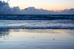 The beach at the sunset with the approaching waves - Image. The beach at the sunset with the approaching blue waves - Image royalty free stock photography