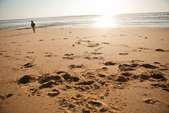 Beach at sunset. Areia Branca beach Portugal at sunset with young girl in background stock photography