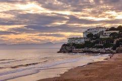 Beach at sunset, beautiful cloudscape, resort, man running along the shore. Stock Photos
