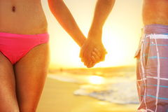 Beach sunset couple in love holding hands romantic Royalty Free Stock Photos
