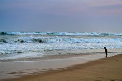 Beach sunset in India. A boy looking into waves during sunset time Royalty Free Stock Images