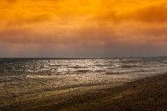 Beach sunset. This is a picture of a summer sunset at the British coast. The sky is cloudy red, there are waves coming to the shingle beach as well as boats, and royalty free stock photos