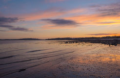 Beach Sunset and Reflections at Low Tide. Whispy Clouds and Orange Sunset Reflected of a Low Incoming Tide in the Early Evening in Scotland Stock Images