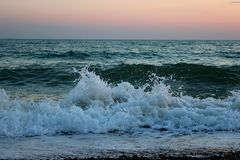 Beach and small waves in the sea, sea foam. Beach at sunset, small waves in the sea, sea foam and spray, as a background royalty free stock photography