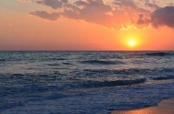 Beach sunset. Sun setting over the sea Stock Image