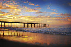Beach sunset sunrise with pier Royalty Free Stock Images