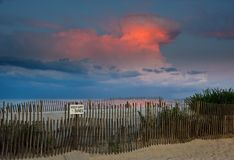 Beach Sunset and Thunderhead. An evening scene at the beach. The last rays of light are dramatically lighting the clouds in the sky of a nearby thunderstorm Royalty Free Stock Photos