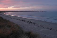 Beach at sunset with town lights in distance Stock Photo