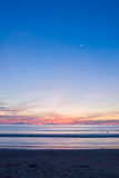 Beach Sunset With A Half-moon Royalty Free Stock Image