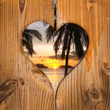 Beach sunset in a wooden heart Stock Images