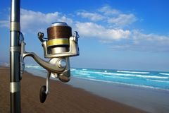 Beach surfcasting spinning fishing reel and rod royalty free stock photography