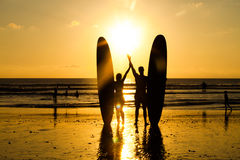 Beach surfer silhouette. Surfer couple in silhouette holding long surf boards at sunset on tropical beach Royalty Free Stock Photos