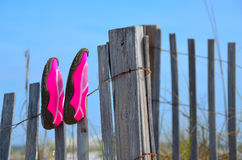 Beach swim shoes drying on fence at Florida beaches Stock Photo