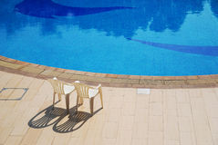 Beach of the swimming pool. Two chairs for sunbathe near the swimming pool Stock Photo
