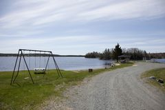 Beach with Swing Set. A little dirt road leads past a small beach with picnic table and swing set stock photos