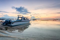 Beach of Tanjong Benoa Bali, Indonesia. Holiday in Bali, Indonesia - Reflection sunrise in Tanjong Benoa with boat Royalty Free Stock Images