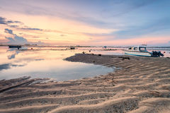 Beach of Tanjong Benoa Bali, Indonesia. Holiday in Bali, Indonesia - Reflection sunrise in Tanjong Benoa with boat Stock Images