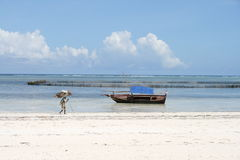Beach in Tanzania. An old woman walking with sticks on a beach in Zanzibar, Tanzania with a boat in the background Royalty Free Stock Photography