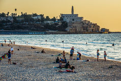 Beach in Tel Aviv. Tel Aviv, Israel - October 21, 2015. People rests on the beach. View with buildings of Jaffa also called Japho or Joppa, former port city, now Stock Photo