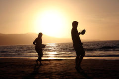 Beach Tennis. Couple play tennis at dusk on the beach Royalty Free Stock Photography