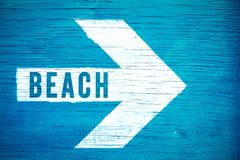 Beach text sign written on a white directional arrow pointing towards right manually painted on a blue wooden signboard Stock Images