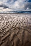 Beach textures at low tide with dramatic sky Stock Image