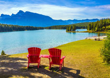 On the beach there are red chaise lounges. The morning sun warms the picturesque lake Two Jack. On the beach there are red chaise lounges. The concept of stock photo
