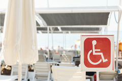 On beach there is sign designating handicapped spot Royalty Free Stock Photography
