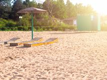 Beach. Three beds under the umbrella. Green dressing room on the backdrop of the cottage royalty free stock photography