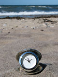 Beach-time!. Chrome clock lying on the beach Stock Image
