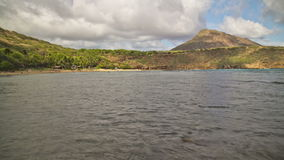Beach Time Lapse Fish. V31. Hanauma Bay Beach Park time lapse clip with fish swimming close by, people snorkeling and on beach, and Koko Head Crater in stock footage
