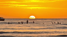 Beach Time Lapse Sunset Pan. V29. Beautiful panning beach time lapse clip of surfers and boats going by during sunset stock footage