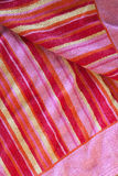 Beach Towel - Background Texture in Stripe Pattern. Background texture of red, yellow, and pink beach towel in colorful stripes design royalty free stock images