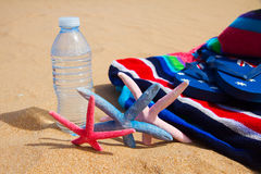 Beach towel and bottle of water on sandy beach Stock Photo