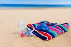 Beach towel and bottle of water on sandy beach. Beach towel and bottle of cool water on sandy beach by sea side Stock Image