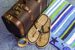 Beach towel, sandals and tropical bangle bracelet beside old vin Stock Photos