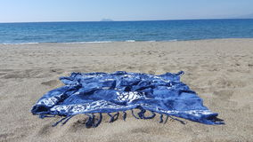 Beach towel. Sandy beach at the cost of Crete Stock Photography