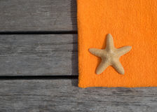 Beach towel and starfish on wood background. Royalty Free Stock Images