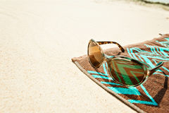 Beach towell on sand with sunglasses Stock Photos
