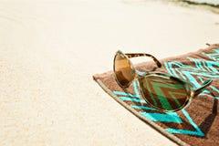 Beach towell on sand with sunglasses Stock Photos