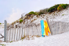 Beach Towels Hanging on a Weathered Wooden Fence. Two multi colored beach towels hang on a weathered wooden fence at a Florida beach royalty free stock photo