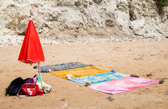 Beach towels and red umbrella in the sand near the sea Stock Photos
