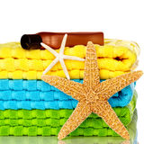 Beach Towels With Starfish And Sunscreen. Blue, Green and Yellow Beach Towels With Starfish And Sunscreen Isolated On White Background Stock Photos