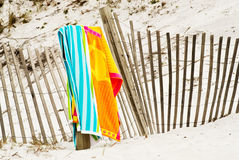 Beach towel. S on a weathered wood picket fence at a sandy beach in florida Royalty Free Stock Image